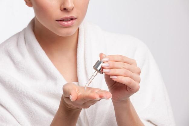 그녀의 손에 치료를 적용하는 매력적인 여자