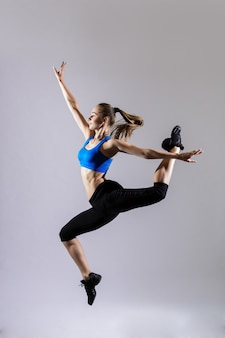 Attractive woman in aquamarine sportswear with ponytail working out on gray background