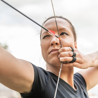 Attractive woman on archery, focuses eye target for arrow from bow