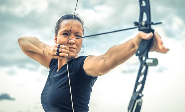 Attractive woman on archery, focuses eye target for arrow from bow.