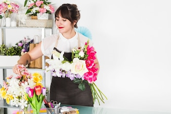 Attractive woman arranging flowers in floral shop