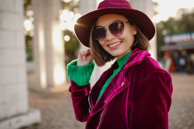 Attractive woman in autumn style trendy outfit walking in street