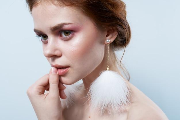魅力的な女性の裸の肩ふわふわイヤリング化粧品のクローズアップ