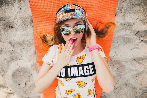 Donna attraente sulla spiaggia che ascolta la musica sulle cuffie in vestito colorato elegante in vacanza tropicale estiva indossando occhiali da sole cappello accessori, sorridente felice sdraiato sulla stuoia di yoga vista dall'alto