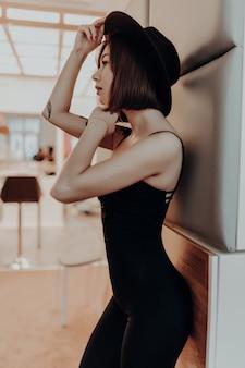 Donna attraente in abito nero e cappello in piedi vicino al muro in appartamento di lusso