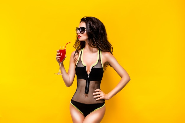 Attractive woman in black monokini with glass of red drink. reto