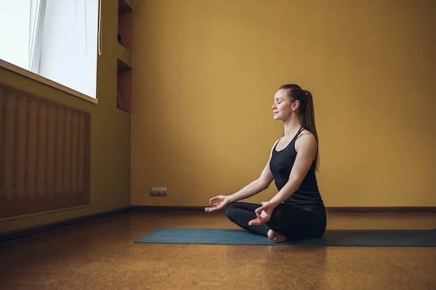Attractive woman in black sportswear practicing yoga is engaged in meditation in the lotus position on a gymnastic mat in the studio near the window