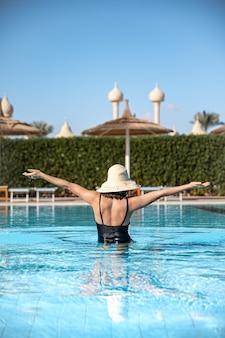 Attraente donna in costume da bagno nero e cappello bagna in piscina.