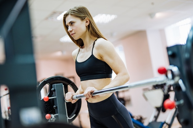 Attractive woman in black top and leggings is standing at the barbell bar in gym. slender sportswoman is doing workout in the fitness center and looking ahead.