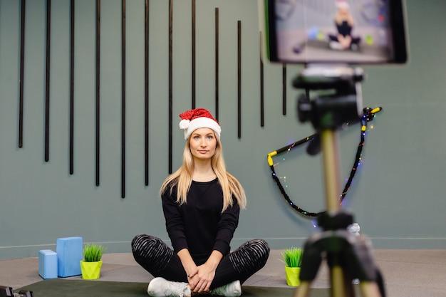 스포츠웨어의 산타 모자에서 매력적인 여성 블로거는 그녀의 동영상 블로그를위한 운동을 기록합니다.