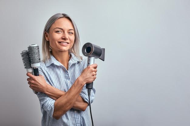 Парикмахер привлекательной женщины белокурый при профессиональный инструмент представляя на камере, серой предпосылке.