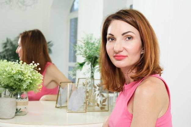 魅力的な女性のブラウスは、鏡に向かって半分回転して寝室の化粧テーブルに座っています