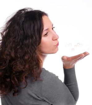Привлекательная женщина, дует сердца на белом фоне