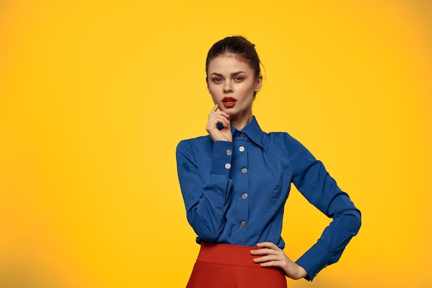Attractive woman in blue shirt gesturing with her hands and red skirt yellow