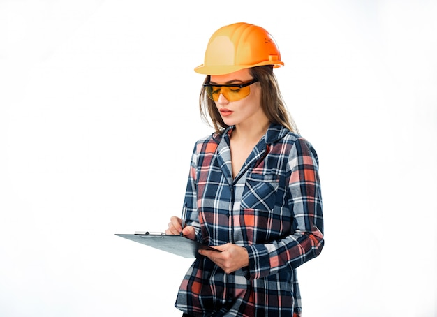 Attractive woman builder in orange helmet and protective glasses with folder in hand writing on white