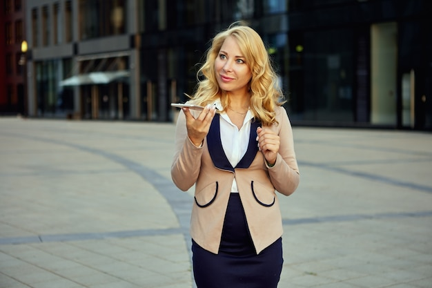 Attractive woman in business suit talking on phone in front of office building
