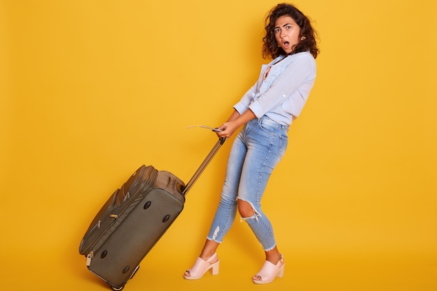 Attractive woman carries heavy suitcase