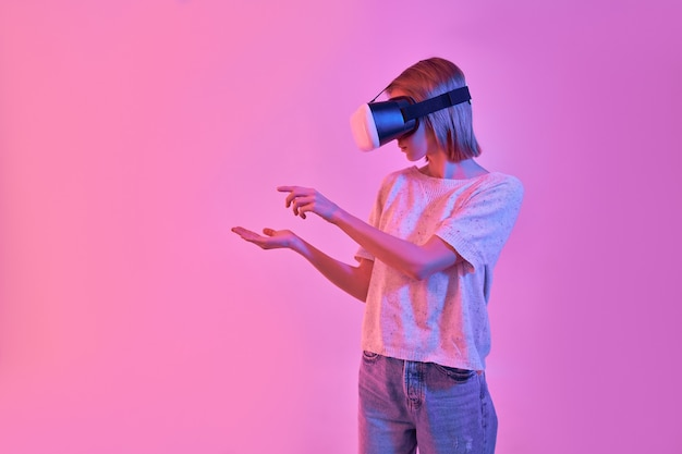 Attractive woman in casual clothes using virtual reality goggles holds something in her palm and tries to touch it isolated on neon pink