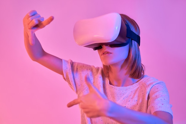 Attractive woman in casual wear using virtual reality glasses, hands gesture frame isolated on neon pink