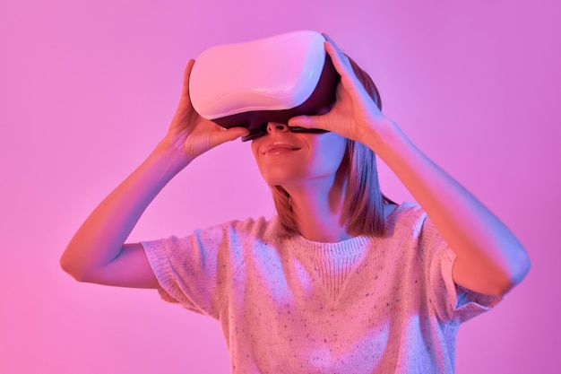 Attractive woman in casual wear using virtual reality glasses isolated on neon pink
