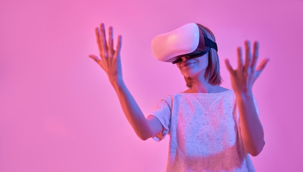Attractive woman in casual wear using virtual reality glasses looks at her hands isolated on neon pink