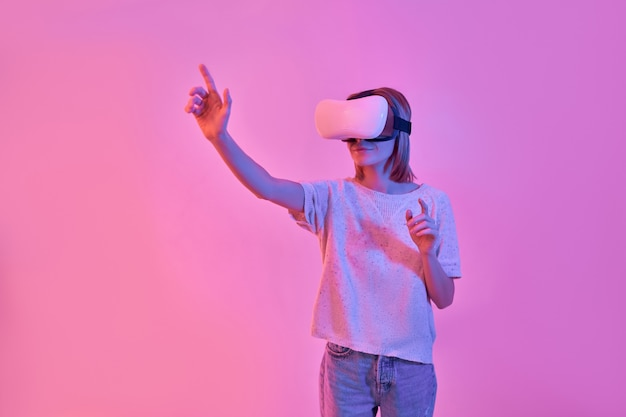 Attractive woman in casual wear using virtual reality glasses presses a virtual button with her finger isolated on neon pink