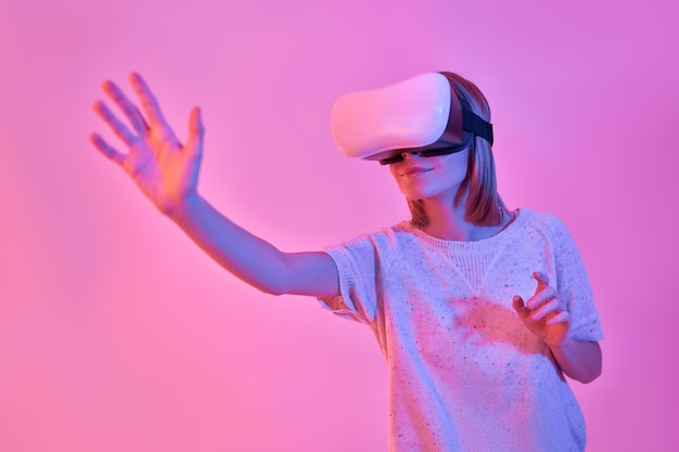 Attractive woman in casual wear using virtual reality glasses, stretching out her palm, trying to touch something, isolated on neon pink