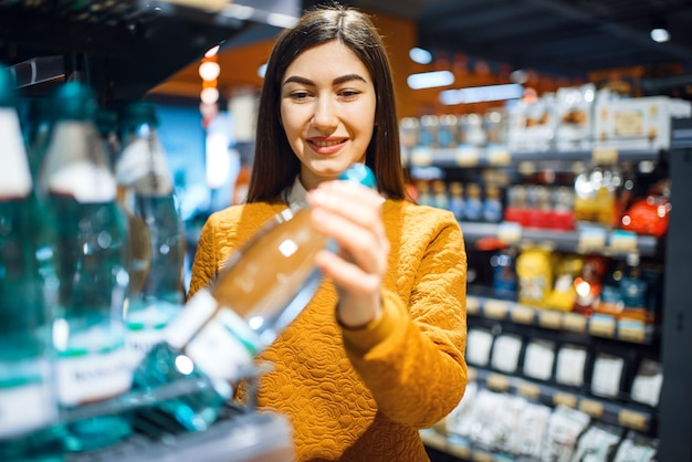 Attractive woman choosing mineral water in grocery store