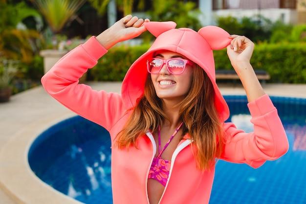 Donna attraente in felpa con cappuccio rosa colorato che indossa occhiali da sole in vacanza estiva sorridente espressione emotiva del viso divertendosi, stile di moda sportiva