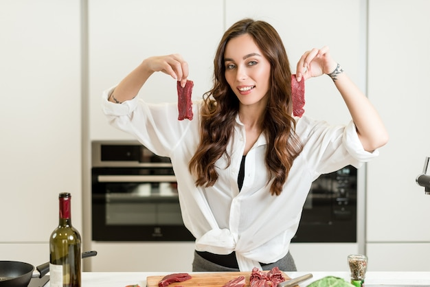 Attractive woman cooking juicy red meat on the kitchen with wine