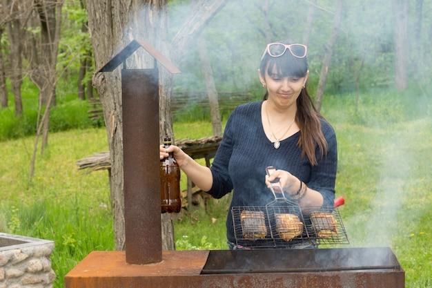 ピクニック バーベキューで料理をする魅力的な女性