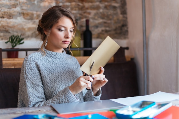 Attractive woman cutting paper