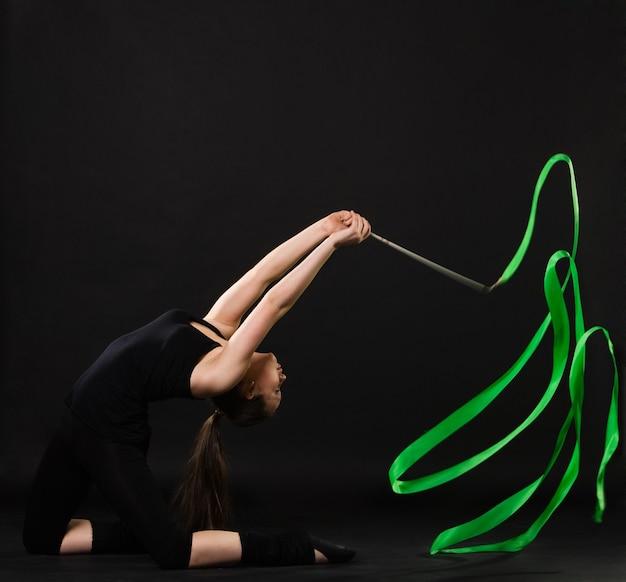 Привлекательная женщина танцует с зеленой лентой на темном фоне
