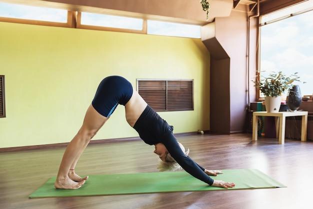 Attractive woman in dark sportswear practicing yoga
