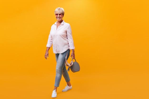 Attraente donna in abito di jeans si muove su sfondo arancione e tiene la borsa
