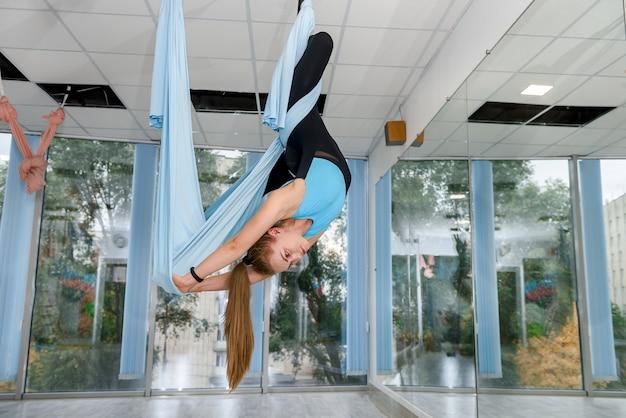 Привлекательная женщина делает упражнения на растяжку аэро-йоги в гамаках в фитнес-студии. здоровый образ жизни для женщин. тренажерный зал