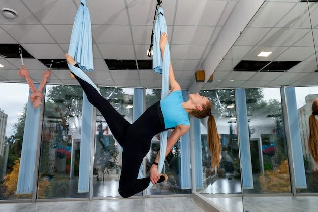 フィットネススタジオのハンモックでエアロヨガストレッチ体操をしている魅力的な女性。女性の健康的なライフスタイル。ワークアウトジム