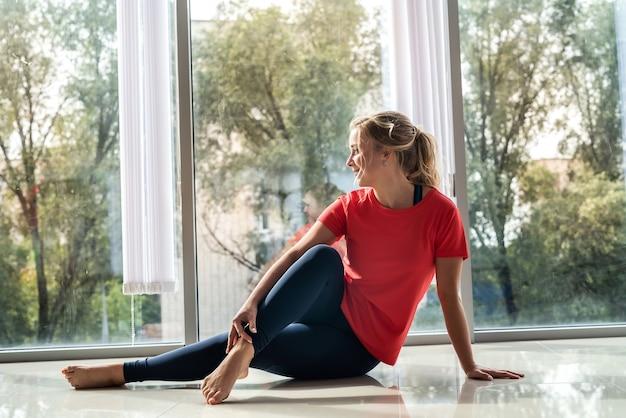Привлекательная женщина делает упражнения йоги пилатес возле окна. здоровый образ жизни
