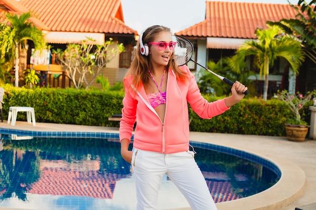 夏休みにヘッドフォンで音楽を聴いてサングラスをかけているカラフルなピンクのパーカーでプールでスポーツをしている魅力的な女性、テニス、スポーツスタイル