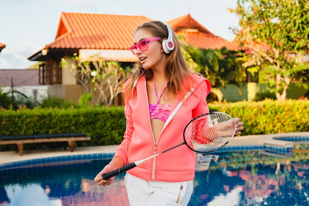 Привлекательная женщина занимается спортом в бассейне в красочной розовой толстовке с капюшоном в солнцезащитных очках, слушая музыку в наушниках на летних каникулах, играет в теннис, спортивный стиль