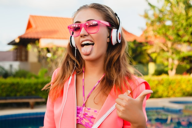 Attractive woman doing sports at pool in colorful pink hoodie wearing sunglasses listening to music in headphones on summer vacation, play tennis, sport style, funny face thumb up
