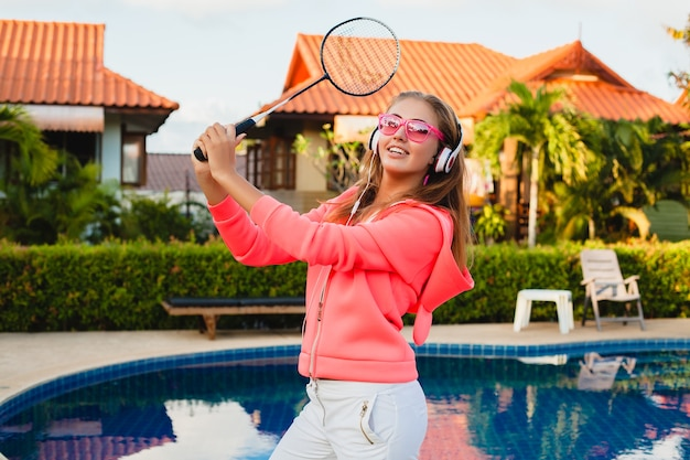 Attractive woman doing sports at pool in colorful pink hoodie wearing sunglasses listening to music in headphones on summer vacation, play tennis, sport style