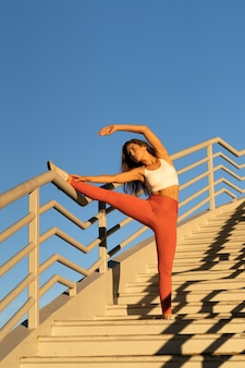 Attractive woman doing stretch exercise outdoor on stairs