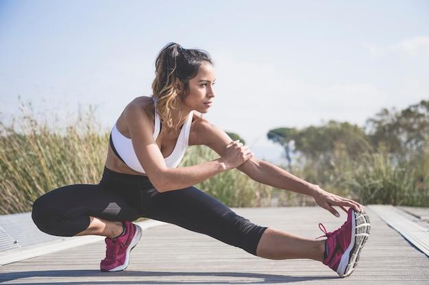 Привлекательная женщина делает упражнения на растяжку на открытом воздухе