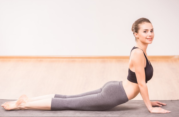 Attractive woman doing upward dog yoga position on mat.