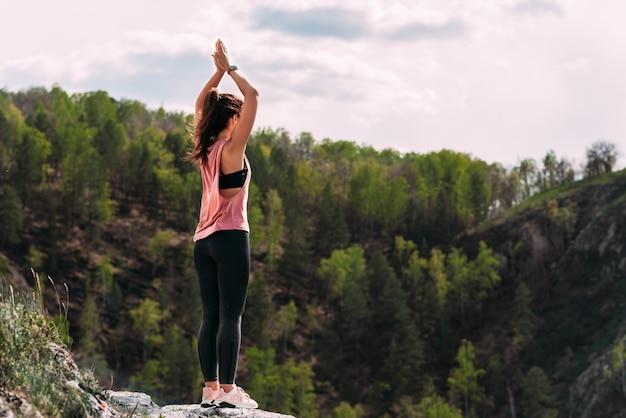 Привлекательная женщина занимается йогой. здоровый образ жизни. концентрация тела. женщина занимается йогой в горах. девушка занимается йогой на рассвете. женщина медитирует на природе. медитация в горах