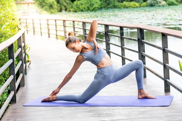 Attractive woman doing yoga on a wooden bridge