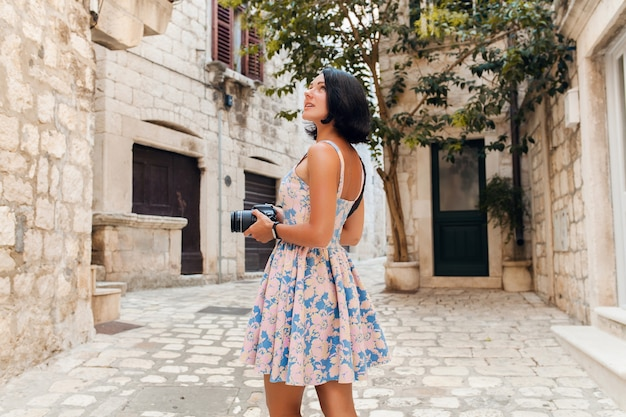 Attractive woman in dress treveling on vacation in old city center of italy taking pictures on camera