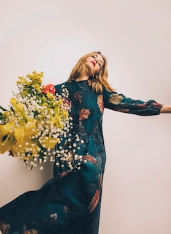 Attractive woman in dress with bouquet of fresh flowers