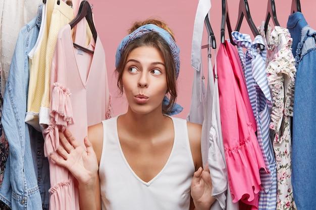 Привлекательная женщина одета небрежно, с сомнением смотрит в сторону, стоя возле вешалки с одеждой, думая, что одеть на деловую встречу с товарищами. модница с большим количеством одежды